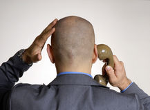 Rear view from a bald head. Rear view from a worry adult bald head man on phone Stock Photo
