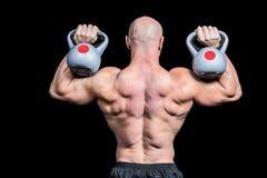 Rear view of bald man lifting kettlebells Royalty Free Stock Image
