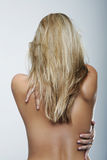 Rear View of a Bare Blond Woman Against Gray Royalty Free Stock Image