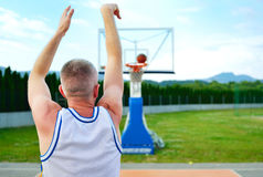 Rear view of a basketball player, shooting at basket outdoor Royalty Free Stock Photo
