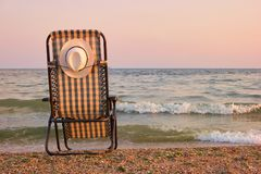 Rear view beach recliner in sea wave background. Deckchair with attached sun hat on the back Stock Photos