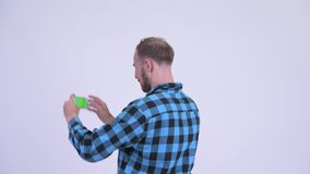 Rear view of bearded hipster man taking picture with phone. Studio shot of bearded hipster man against white background stock video footage
