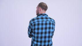 Rear view of bearded hipster man thinking and waiting. Studio shot of bearded hipster man against white background stock footage