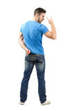 Rear view of bearded man with heavy metal hand sign Stock Image