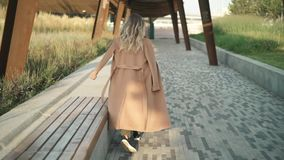 Rear view of beautiful blonde woman walking, turning around and smiling