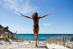 Rear view of a beautiful, brunette young girl with raised hands, looking at ocean. royalty free stock images