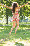 Rear view of beautiful stylish brunette jumping in the air Royalty Free Stock Photo