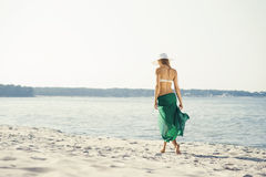 Rear view of beautiful woman in green silk walking. Along the seacoast Stock Photos