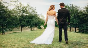 Newlywed couple walking together in park. Rear view of beautiful young bride in a wedding dress holding the hand of the groom and walking in park. Couple holding Stock Photo