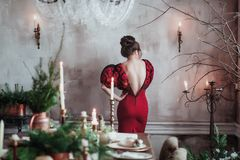 Rear view beautifull young woman stands against grey wall in red dress near served table with candles and fir branches. Christmas eve in restaurant Royalty Free Stock Image
