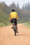 Rear view of bicycle man riding on dirt road with drinking water royalty free stock image