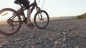 Rear view of a black mountain bike on which the guy rides for a walk 8-9 years. A child who rides a bicycle in the hills. Area at sunset in summer, slow motion stock footage