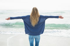 Rear view of a blond with arms outstretched at beach Royalty Free Stock Image