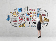 Rear view of a blond businesswoman in a black skirt drawing a colorful  business idea sketch. Royalty Free Stock Images