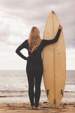 Rear view of a blond in wet suit with surfboard at beach Stock Images