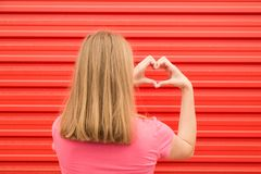 Back view of young female making heart shape on red wall. Love concept. stock photography