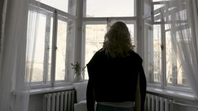 Rear view of blonde in black cardigan on her shoulders moving slowly to the window at home in bright room. Action. Young royalty free stock images