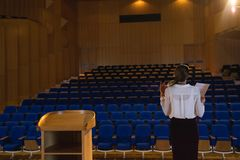 Businesswoman practicing and learning script while standing in the auditorium. Rear view of blonde Caucasian businesswoman practicing and learning script while royalty free stock photo