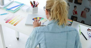 Rear view of blonde designer working at her desk stock footage