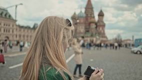 Blonde tourist taking pictures of Saint Basil`s Cathedral, Moscow Russia. Rear view of a blonde young tourist wearing a green coat making photos of Saint Basil`s stock footage