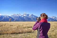 Rear view of blurred woman taking pictures with DSLR camera. Stock Image