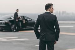 Rear view of bodyguard in suit. And sunglasses stock photo