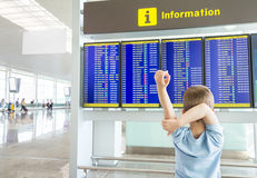 Rear view of bored kid looking panel flight times Stock Photo