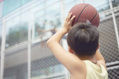 Rear view of boy aiming basketball hoop before shooting Stock Photography