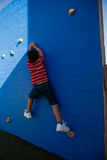 Rear view of boy climbing blue wall at playground Stock Photography