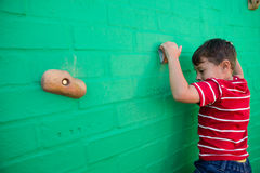 Rear view of boy climbing wall at playground Stock Image