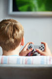 Rear View Of Boy Holding Controller Playing Video Game Stock Photos
