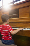 Rear view of boy playing piano in classroom Stock Photos