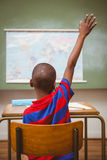 Rear view of boy raising hand in classroom. Rear view of little boy raising hand in the classroom Royalty Free Stock Image