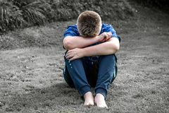 Rear View of a boy Sitting on Grassland stock images