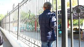 Rear  view of a boy walking on metal fence stock video
