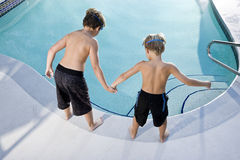 Rear view of boys looking in swimming pool. Boys, 7 and 9, looking down at water in swimming pool Stock Image
