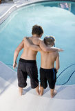 Rear view of boys looking in swimming pool. Boys, 7 and 9, looking down at water in swimming pool Royalty Free Stock Photos
