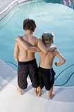 Rear view of boys looking in swimming pool. Boys, 7 and 9, looking down at water in swimming pool Royalty Free Stock Photo