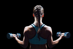 Rear view of braided hair woman lifting dumbbells Stock Image