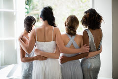 Rear view of bride and bridesmaids standing together near window. At home royalty free stock photos