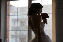 Rear view of bride silhouette near the window smells the red flowers.  royalty free stock image
