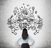 A rear view of a brunette business lady who is looking at the concrete wall with the drawn sketch about business ideas and develop. Ment of business plan Stock Photos