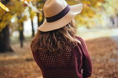 Rear view of brunette girl in autumn fall park in brown hat, sweater and trousers. Back view of autumn portrait of woman stock image