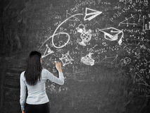 Rear view of a brunette lady who is drawing a graduation sketch. Math formulas, an arrow and geometric figures are drawn on the bl Royalty Free Stock Photo