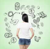 A rear view of a brunette lady who is trying to make a choice in favour of a certain sport activity. Blue sport icons are drawn on Royalty Free Stock Images