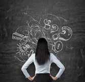 Rear view of brunette who is looking at the black chalkboard with drawn sketch of business icons, exclamation and question marks. Royalty Free Stock Image