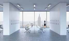 Rear view of a brunette who is looking out the window in a modern panoramic office. Stock Photos