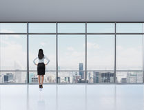 Rear view of brunette woman in the office who looks through the window. Royalty Free Stock Images