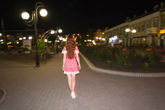 Rear view of a brunette woman walking near a park at night. Shining lights Stock Image