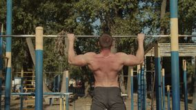 Athletic man making pull-up exercises on crossbar
